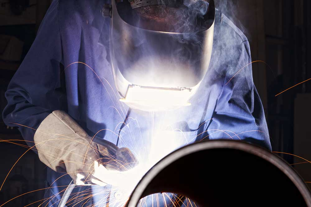 welder welding pipe with sparks flying around him