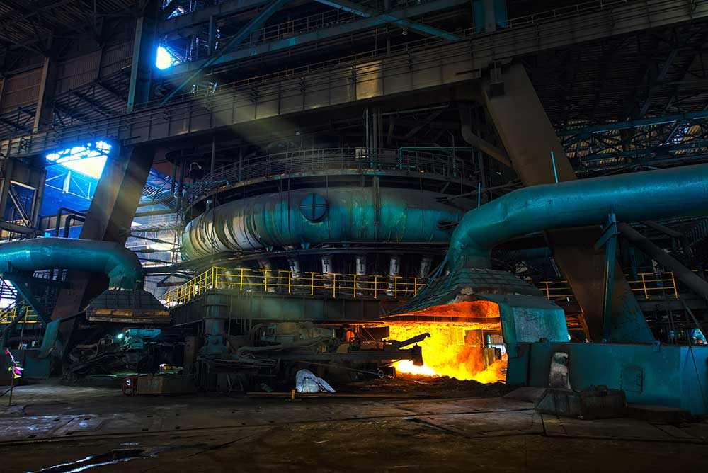inside of a steel mill with glowing melting steel and blue colored pipes